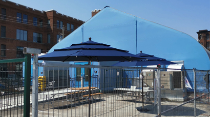 Temporary structures used as a Respite Centre for the City of Toronto. Umbrellas were donated to make outdoor sitting more pleasant.